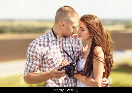 Girl and guy lovingly look at each other on a summer sunny day on the street - Stock Photo