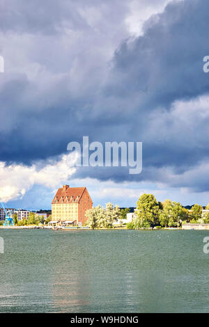 Old warehouse as a hotel on Ziegelsee in Schwerin under dramatic clouds. Mecklenburg-Western Pomerania, Germany - Stock Photo