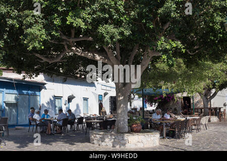 Tilos island, Greece - September 22, 2018. Livadi village square, local men and tourists sit at outdoors traditional cafe bar in the summer morning un - Stock Photo