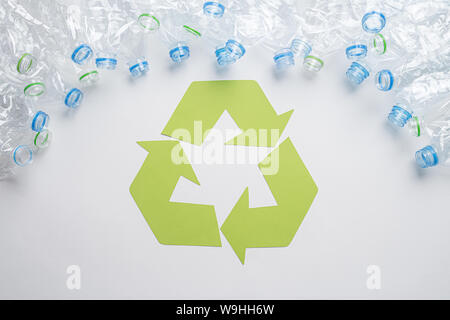 Frame of used plastic bottles with recycling symbol on wooden background. Recycle concept