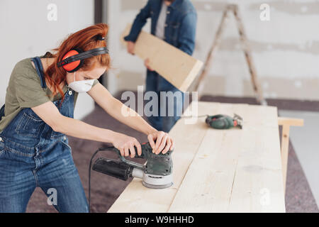 Capable young woman sanding planks of wood with an orbital sander in an unfinished room during DIY renovations - Stock Photo