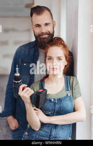 Capable young couple doing DIY renovations to their new home posing together with the woman holding an electric drill in her hand - Stock Photo