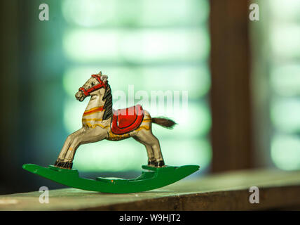 wooden antique miniature rocking horse swinging in a window sill - Stock Photo