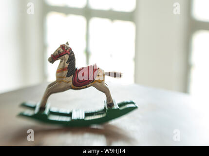 wooden antique miniature rocking horse swings on a table - Stock Photo