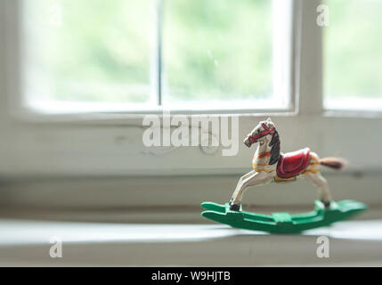 wooden antique miniature rocking horse swinging in the window sill of an old white wooden window - Stock Photo