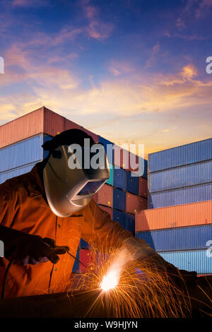 Industrial welding worker welding steel structure with cargo container stack in background - Stock Photo