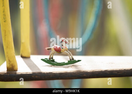 wooden antique miniature rocking horse at a colorful playground with rope swings - Stock Photo