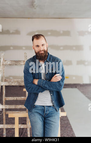 Smiling attractive young bearded man with folded arms sitting on a wooden trestle in an unfinished room during renovations smiling at the camera - Stock Photo