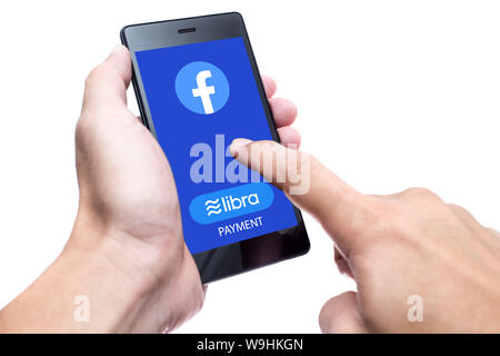Facebook Libra coin logo icon on  smartphone screen on white background, new internet currency using blockchain for modern world payment and bacnking. - Stock Photo