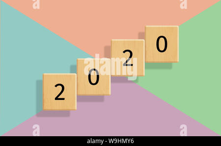 The year 2020 on floating wooden tiles against colorful pastel background - Stock Photo
