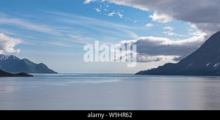 summer clouds gather over the mouth of disenchantment bay in yakutat bay in alaska with the tip of haenke island on the left - Stock Photo