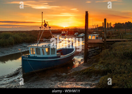 Grounded boats waiting for the tide to come in at Thornham near Hunstanton Norfolk with the sun rising in the background - Stock Photo