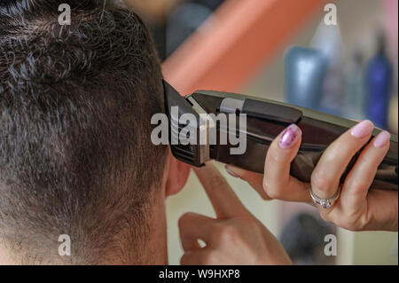 Hands of barber trimming hair with clipper, close up rear view. Barbershop concept. Man in hairdressers chair. Hipster client getting hairstyle. - Stock Photo