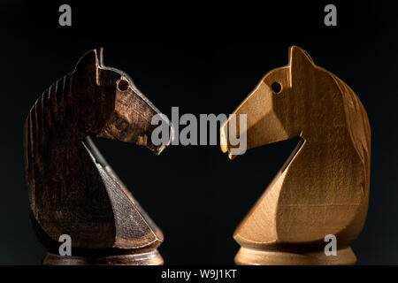 close view of white and black chess knights facing on blackground. - Stock Photo