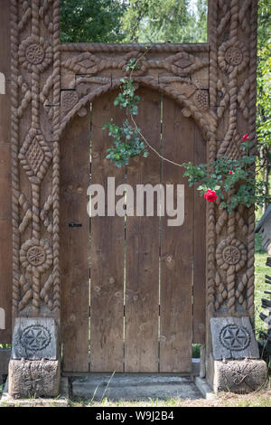 Maramureș, northern Rpmania. A typical carved wooden gate in the village of Botiza, in this highly traditional rural region - Stock Photo