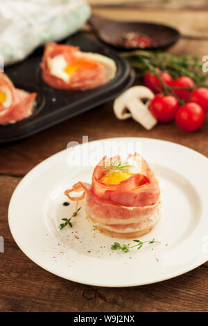 Delicious egg muffins wrapped in crispy bacon served on white plate on wooden background - Stock Photo