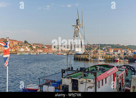 Whitby harbour and marina in the evening light.  A fishing trawler and flag is in the foreground and buildings line the shore. A blue sky is overhead. - Stock Photo