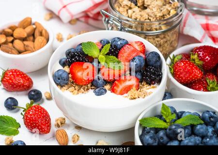 Greek yogurt granola with fresh berries on white table. - Stock Photo