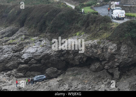 Swansea, Wales, UK. 14th August, 2019.  A damaged car remains stranded at the bottom of cliffs at Limeslade Bay, near Mumbles, Swansea, south Wales after it plunged into the sea on Tuesday morning. The driver was taken to hospital and detained under the Mental Health Act but was not seriously hurt.  Credit : Robert Melen/Alamy Live News. - Stock Photo