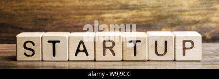Wooden blocks with the word Startup. Temporary structure designed to find and implement a scalable business model. The concept of raising funds for a - Stock Photo