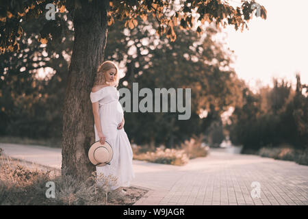 Beautiful pregnant woman 20-24 year old standing in park over sun light. Wearing elegant white dress and holding straw hat outdoors. Motherhood. Mater