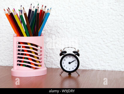 black alarm clock with arrows and color pencils on a wooden table, close-up - Stock Photo