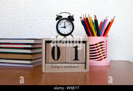 intermittent wooden calendar with the date of the first of September and an alarm clock, colored pencils on the table, a reminder of the school, close - Stock Photo