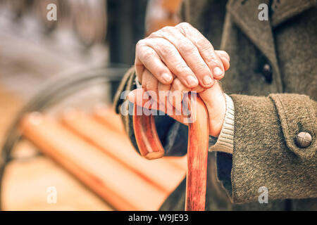 Close up of hands of elderly man leaning on cane - Stock Photo