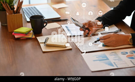 Cropped shot businesswoman using smartphone and innovation technology in smart device on office desk. - Stock Photo