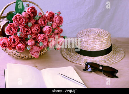 notebook with a pen, straw hat and a bouquet of roses in a wicker basket on the table, on a light background - Stock Photo