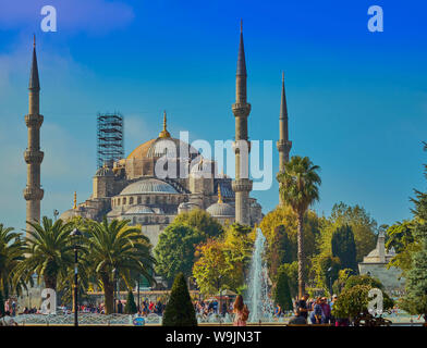 Istanbul, Turkey, September 23., 2018: Hagia Sofia behind the park in front of the Blue Mosque in bright sunshine with tourists in front of the founta - Stock Photo