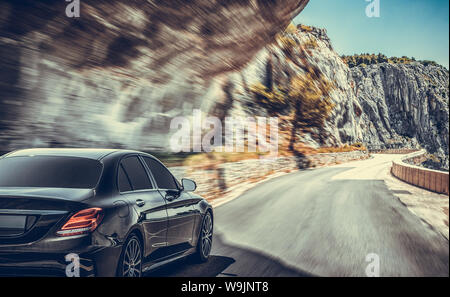 The car moves on a mountain road on a summer sunny day. - Stock Photo