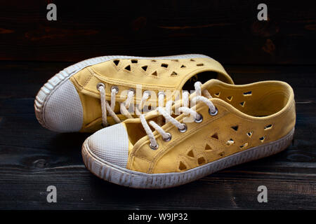 pair of used old fashioned yellow sneakers shoes on dark wooden surface - Stock Photo