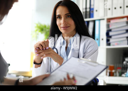Female visitor filling out medicine documents - Stock Photo