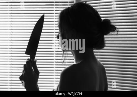 Silhouette of sad woman's head with waving hair holding a knife. concept kill - Stock Photo