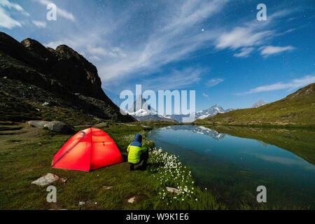Hiker beside tent looking towards the Matterhorn from lake Riffelsee, Zermatt, canton of Valais, Swiss Alps, Switzerland, Europe - Stock Photo