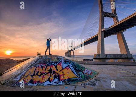 A tourist admires the majestic Vasco da Gama Bridge over the River Tagus, Parque das Nacoes, Lisbon, Portugal, Europe - Stock Photo