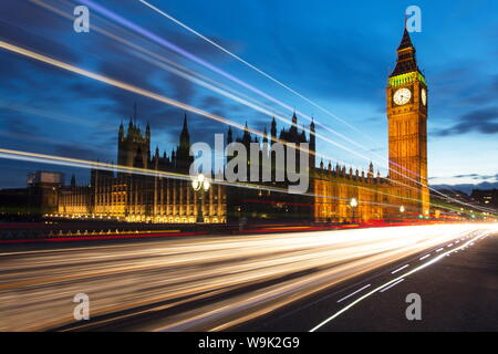 Houses of Parliament and Big Ben floodlit at night with colourful light trails from passing traffic on Westminster Bridge, London, England, UK