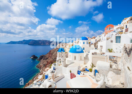 Greek church with three blue domes in the village of Oia, Santorini (Thira), Cyclades Islands, Greek Islands, Greece, Europe - Stock Photo