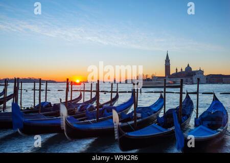 Gondolas and San Giorgio Maggiore Church across Bacino di San Marco, sunrise on Venice lagoon, Venice, UNESCO World Heritage Site, Veneto, Italy - Stock Photo