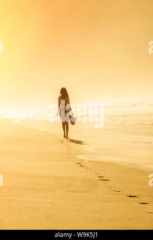 Young Brazilian (Latin American) (Latina) woman in golden dawn light on the beach in a bikini, Rio de Janeiro, Brazil, South America - Stock Photo