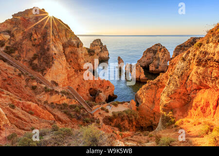 Golden sunrise on the red cliffs of Ponta Da Piedade, Lagos, Algarve, Portugal, Europe - Stock Photo