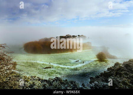 A lady walking her dog along a footpath below Eddisbury Hill on a frosty winters morning with fog and mist clearing beyond, Cheshire, England, UK - Stock Photo