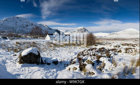 Panoramic view of Black Rock Cottage with Buachaille Etive Mor in distance on snow covered Rannoch Moor, near Fort William, Highland, Scotland, UK - Stock Photo