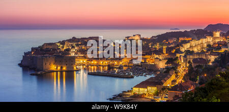 Aerial panorama of Dubrovnik Old Town at night with orange sunset sky, UNESCO World Heritage Site, Dubrovnik, Dalmatian Coast, Croatia, Europe - Stock Photo