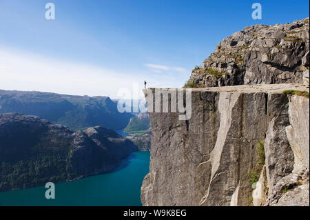 Man standing on Preikestolen (Pulpit Rock) above fjord, Lysefjord, Norway, Scandinavia, Europe - Stock Photo