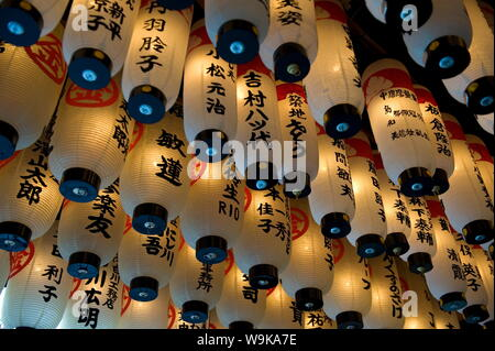 Lanterns with donors names hanging from the ceiling at Hozenji Temple in Namba, Osaka, Japan - Stock Photo