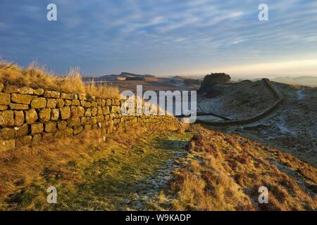 Sunrise and Hadrian's Wall National Trail in winter, looking to Housesteads Fort, Hadrian's Wall, UNESCO, Northumberland, England, UK - Stock Photo