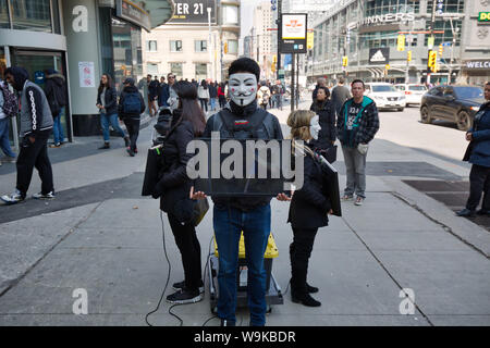 Toronto, Ontario, Canada-20 March, 2019: Protest against animal cruelty by a group of young activists wearing anonymous masks and holding TV sets that - Stock Photo