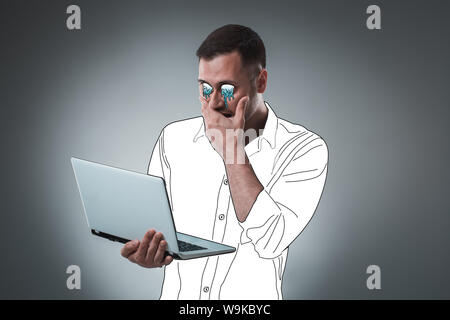 Handsome young man with a cartoon eyes and shirt is holding a laptop, looking at it and acting like he is shocked. - Stock Photo